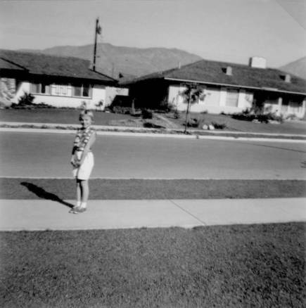 Sheryl Koncsol in front of house at 1034 Maryhurst in 1964